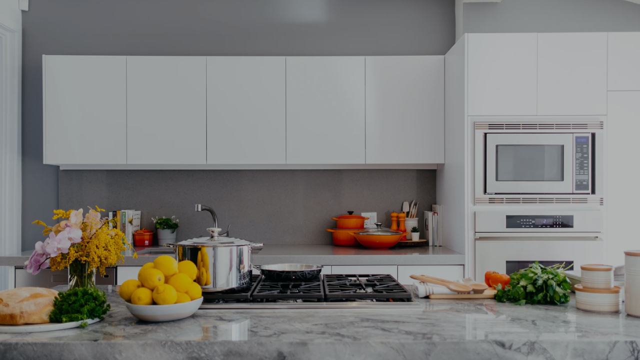 A white and grey modern kitchen with a cooktop, lemons, flowers and orange pots