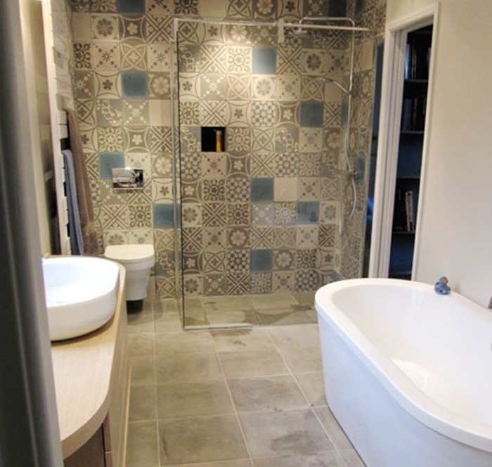 Mosaic tiled bathroom with a white ceramic toilet and sink.