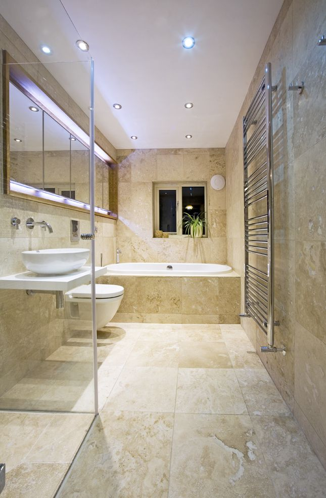 Yellow marble bathroom with a white bathtub, sink and toilet
