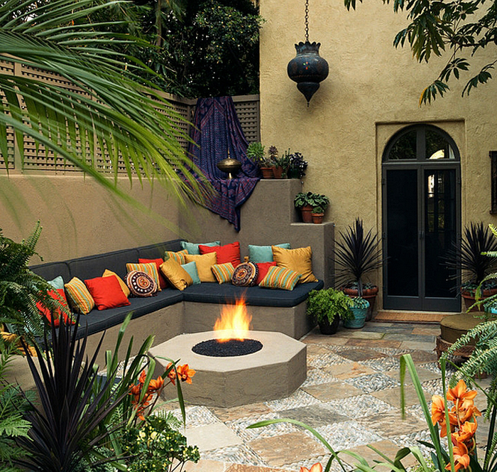 An outdoor fireplace in a garden with couches and multicoloured pillows.