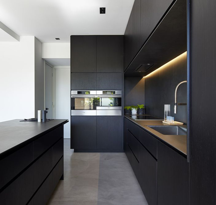 A spacious and modern black and grey kitchen with dual ovens, warm lighting and a sink